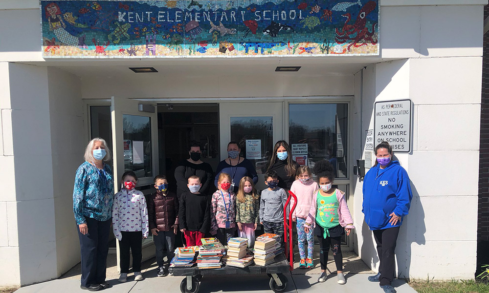 Kent Elementary students pose at the school entrance with a cart of donated books