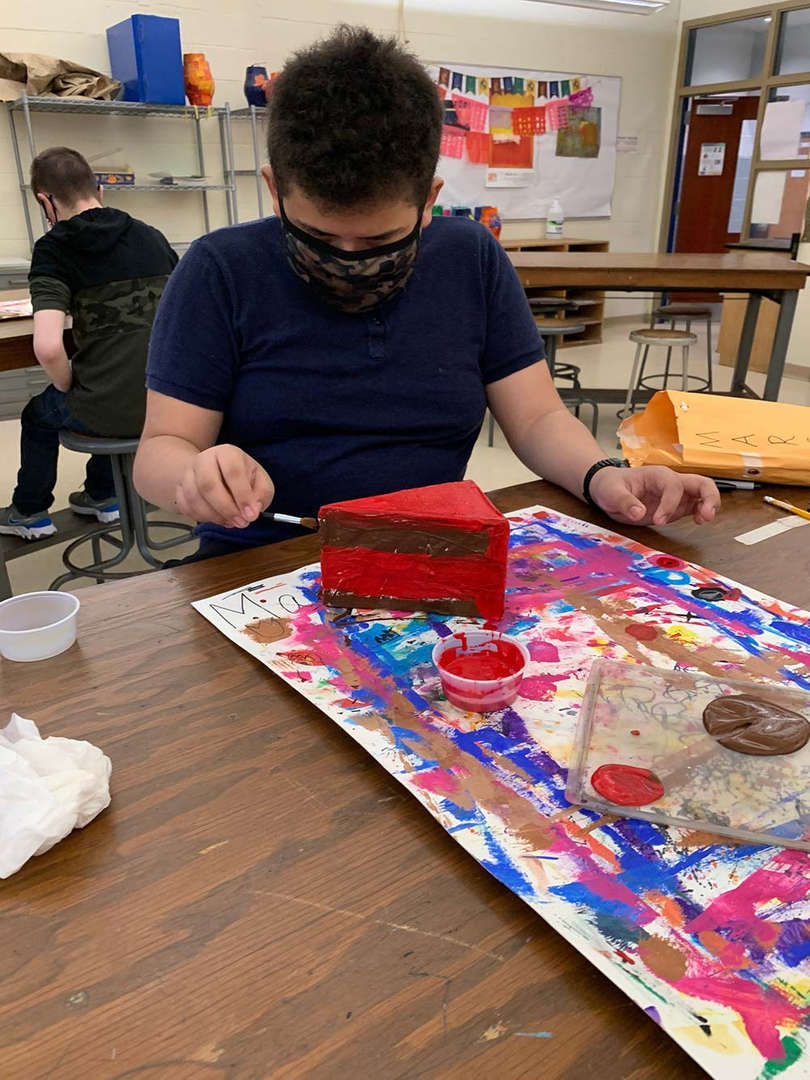Student painting a red slice of cake artwork