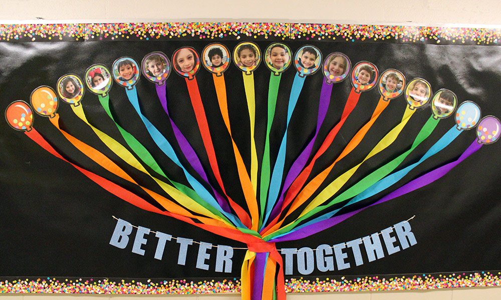 Bulletin board featuring student photos that says: Better together!