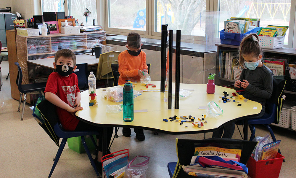 Kindergarten students sit around a table with barriers between them.