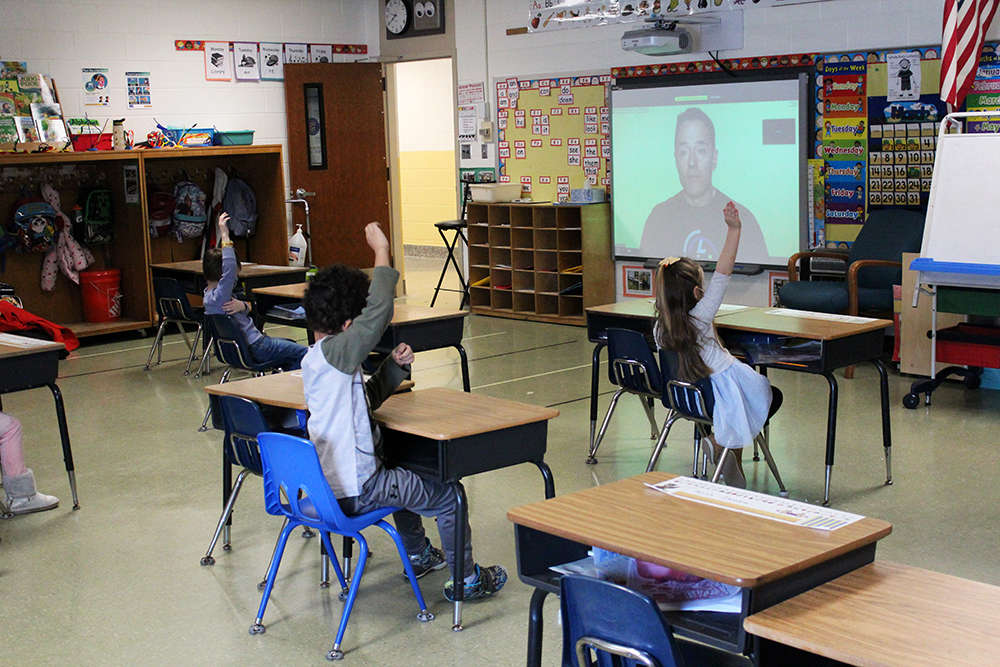 Kindergarten students raise their hands to answer a question during a virtual weather assembly