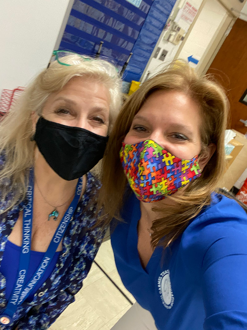 Two women wearing blue shirts and face masks