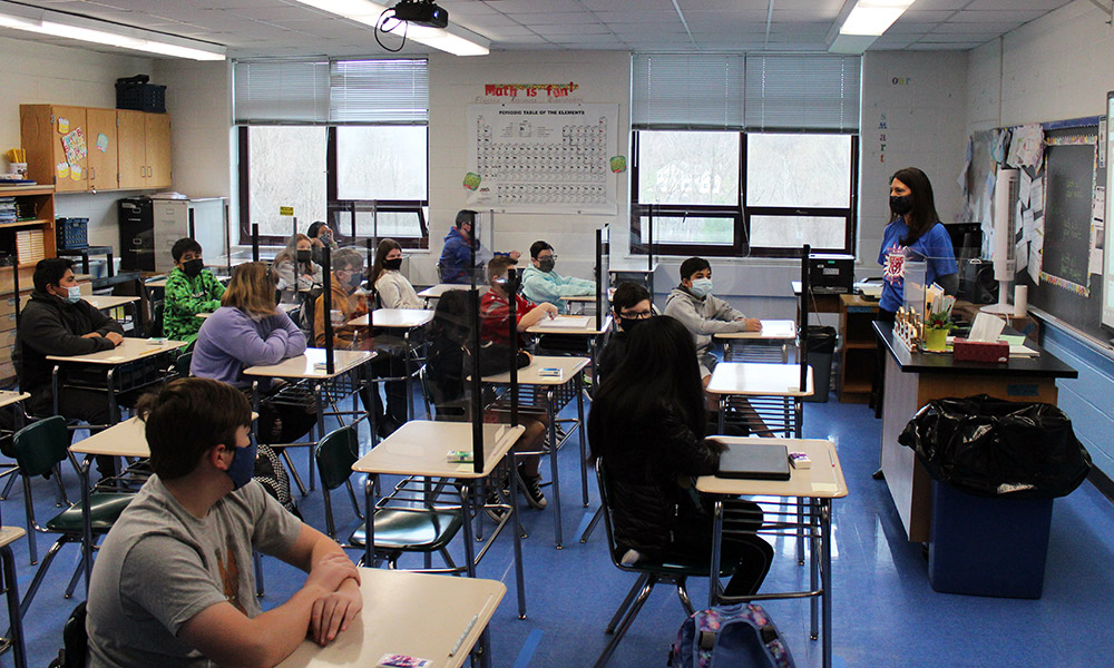 Students sit at desks behind barriers in the classroom.