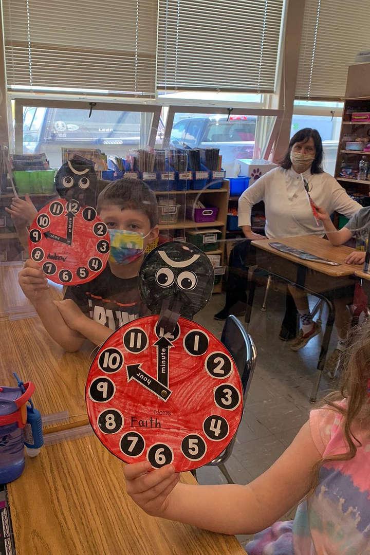 Students hold up their ladybug clocks at their desks.