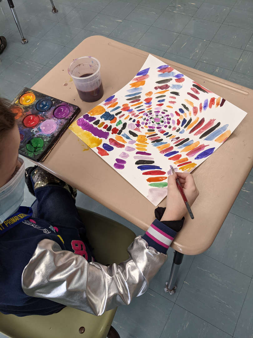 Student creating a painting at their desk