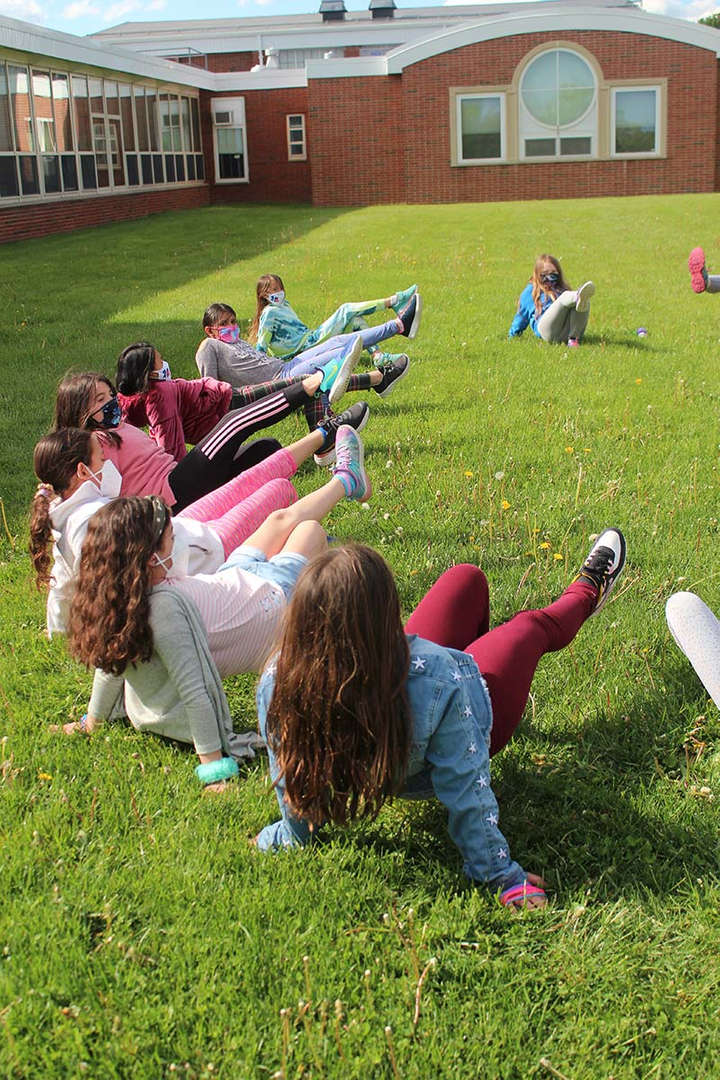 Students sit on the ground and stretch their legs before running.