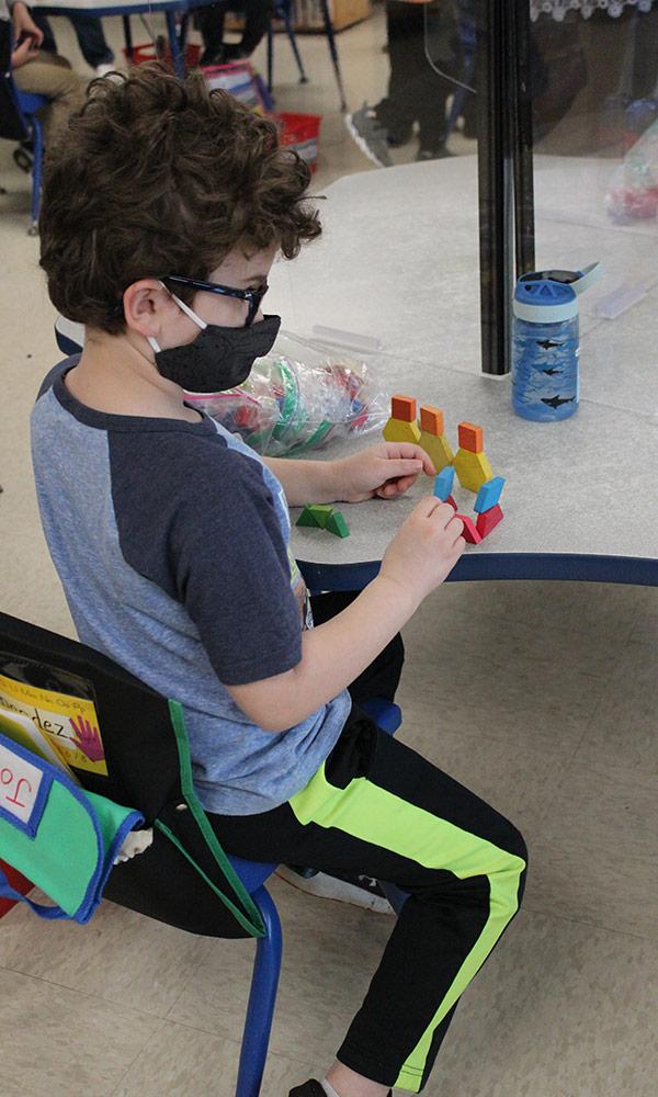 Kindergarten student works at desk with barriers around him.
