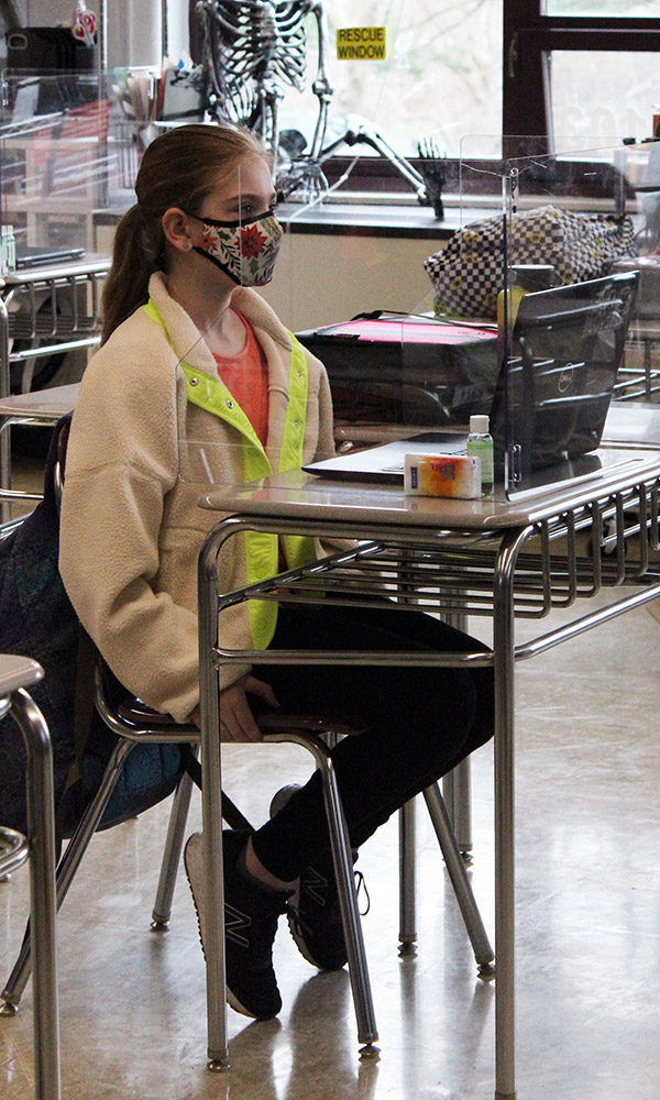 Student sits at a desk behind a barrier.