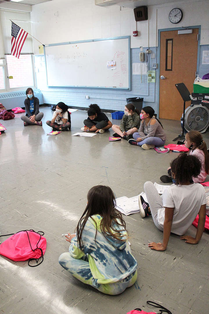 Group of girl students sit on floor in a circle during a lesson.