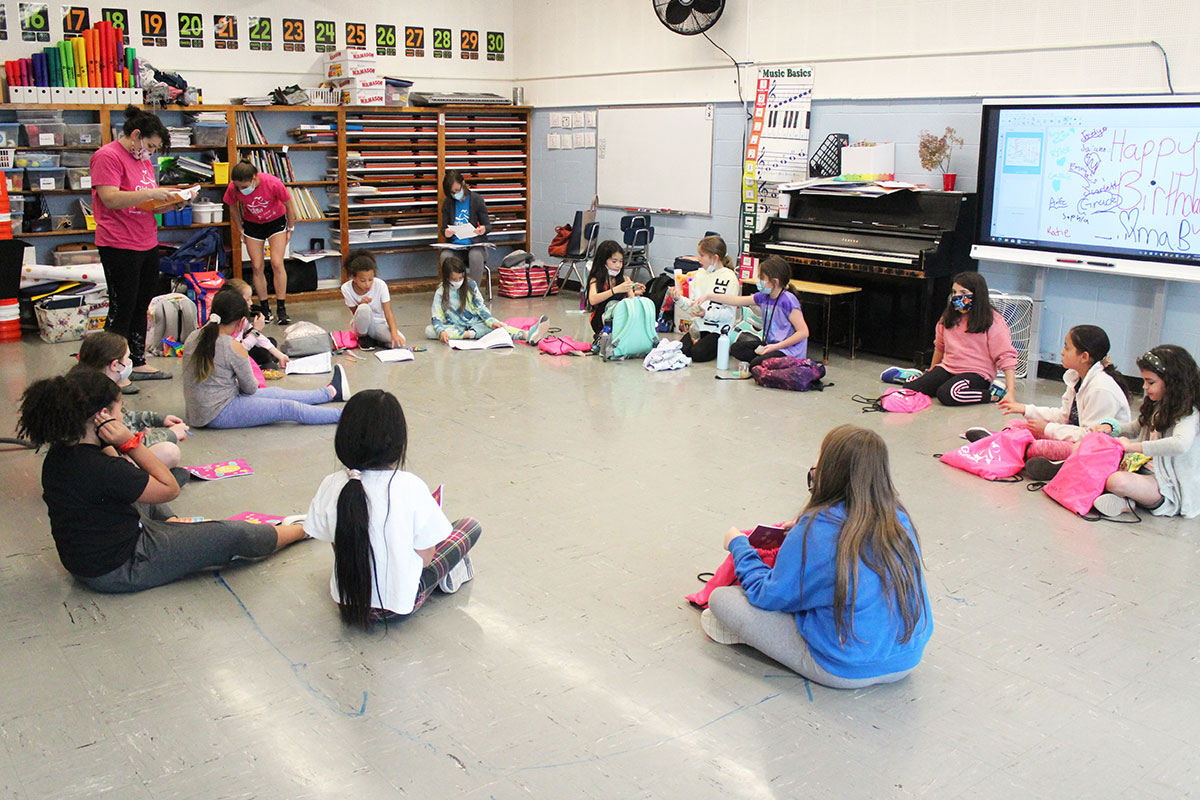 Students sit in circle on the floor waiting for lesson to begin.