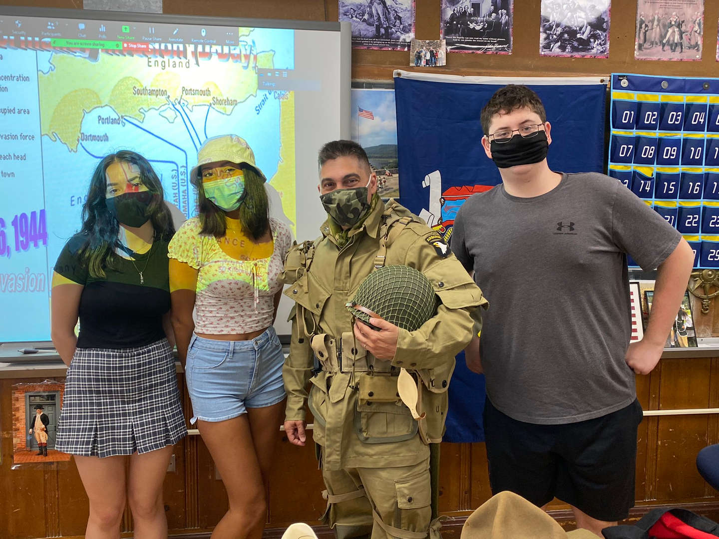 Students stand with a teacher dressed as a soldier for a lesson on WWII D-Day