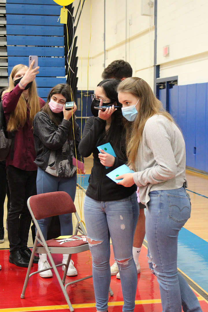 Students listen to video clues on their phones