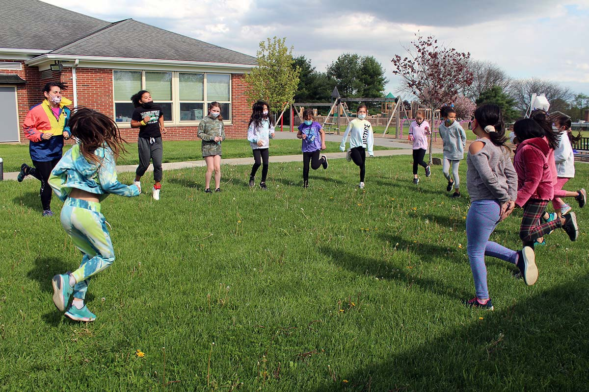 Students job in place during warm-up exercises before running.