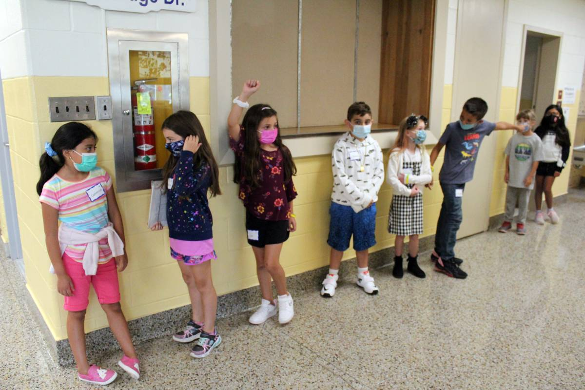Students line up against a wall in the hall of Kent Primary