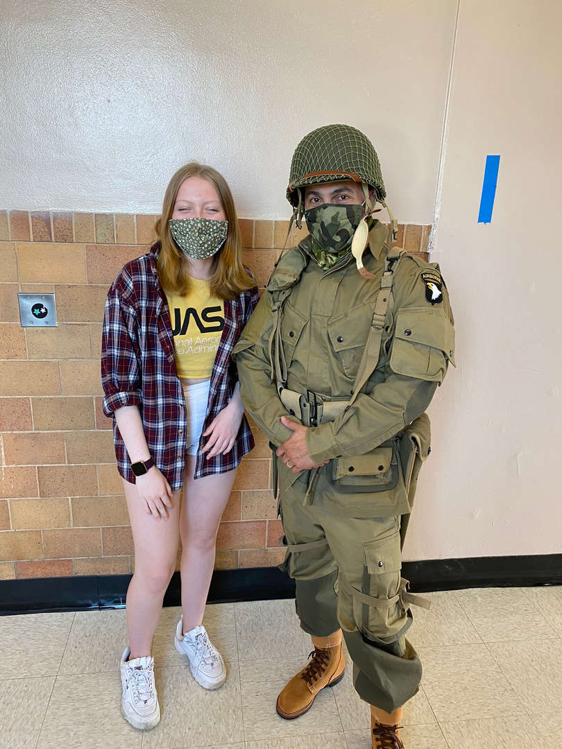 A student stands with a teacher dressed as a soldier for a lesson on WWII D-Day
