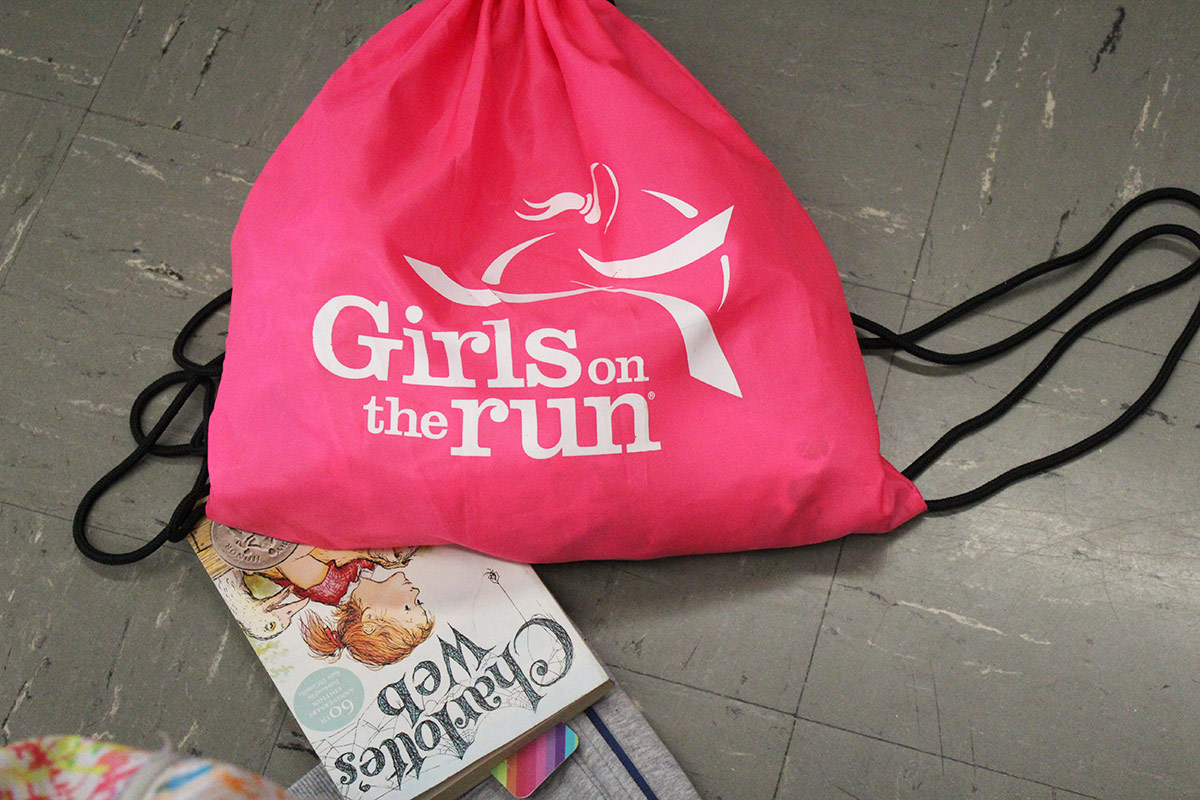 Pink Girls on the Run bag next to a copy of Charlotte's Web book on the floor.