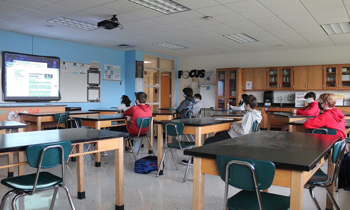 Large group of science students watching presentation at the front of the room on a screen