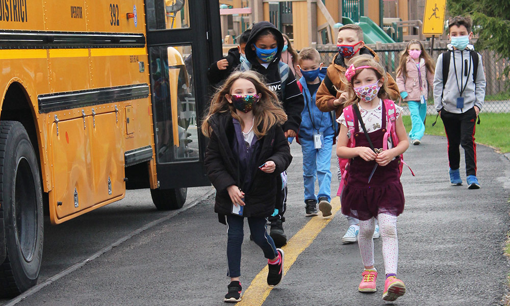 Students enter Kent Elementary School from buses.