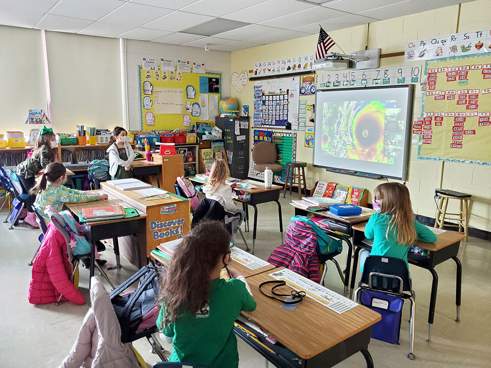 Students view an image of a hurricane during a weather presentation