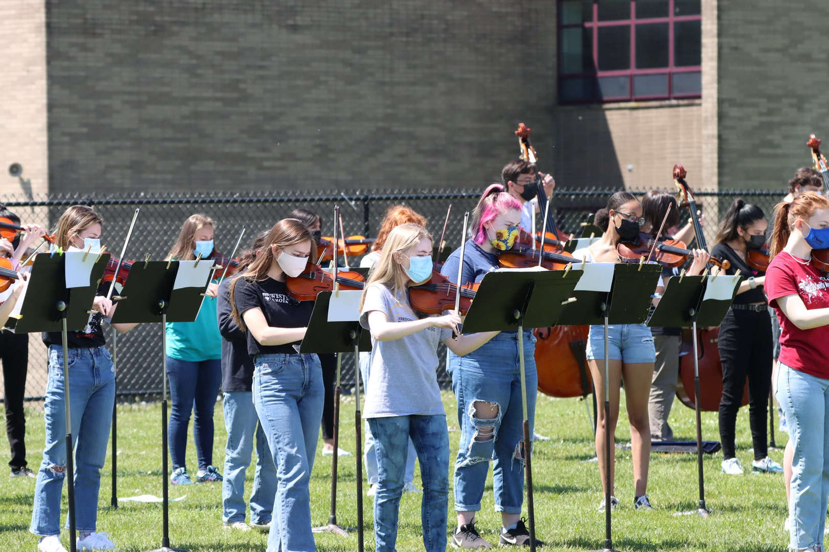 Student musicians playing outside on the field.