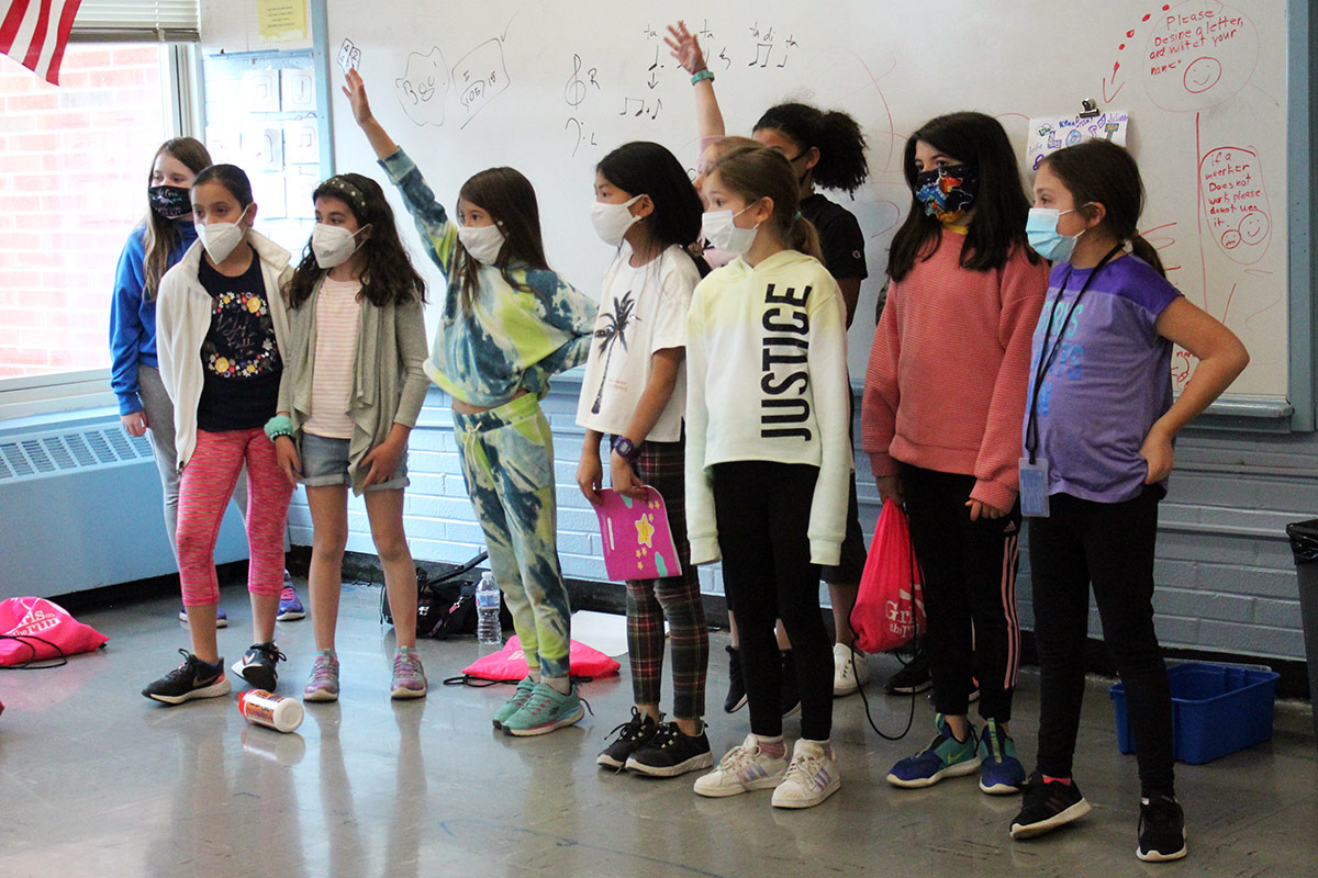 Group of students raise hands to answer questions during a lesson.