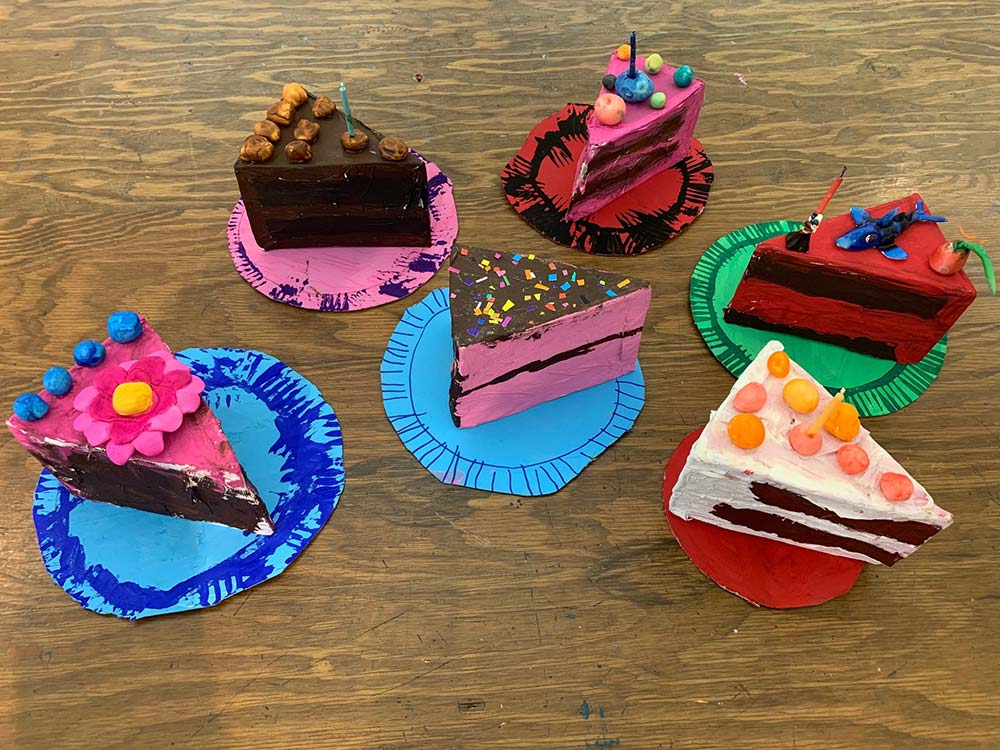 Six slices of cake artwork on table