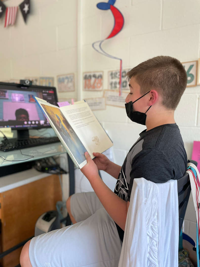 A male student reads The Last Brother - A Civil War Tale to another student on Zoom.