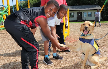 students interact with therapy dog on playground