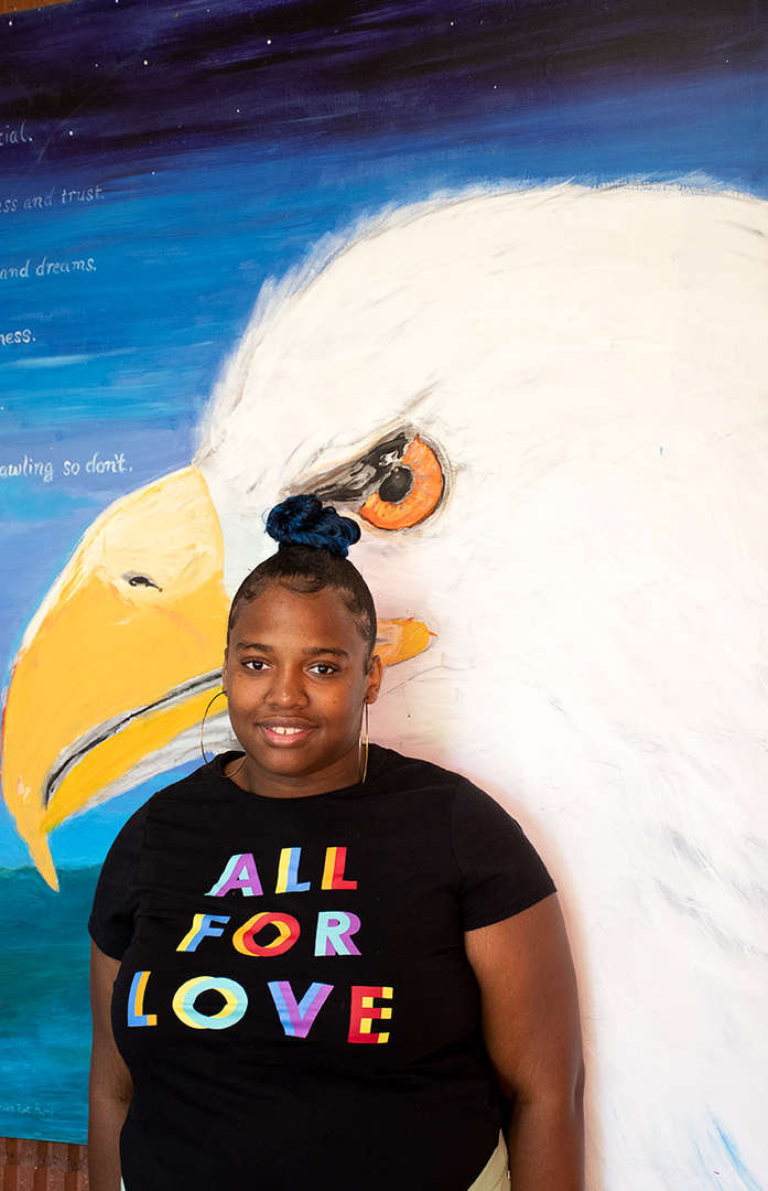 student posing in front of bald eagle mural