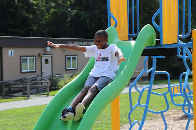 student going down a playground slide
