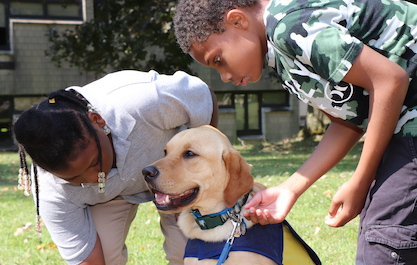 students meeting therapy dog on playground