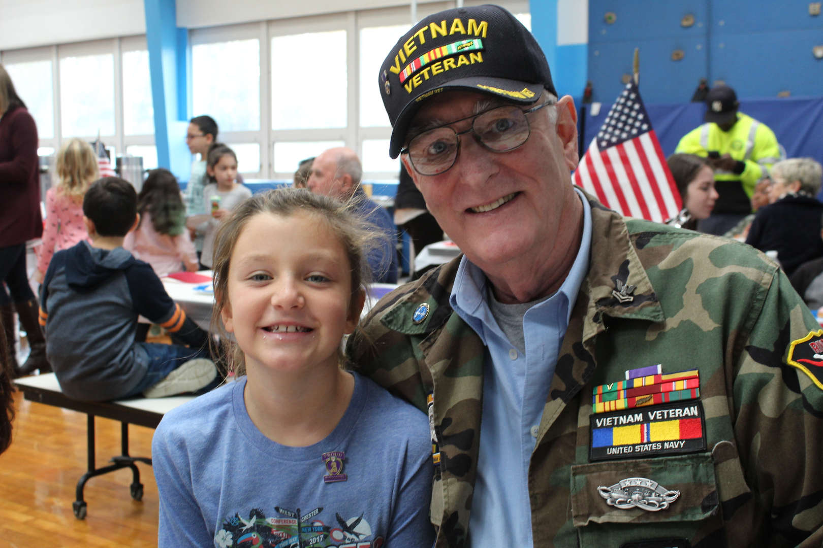 Veteran with hat sits with young girl