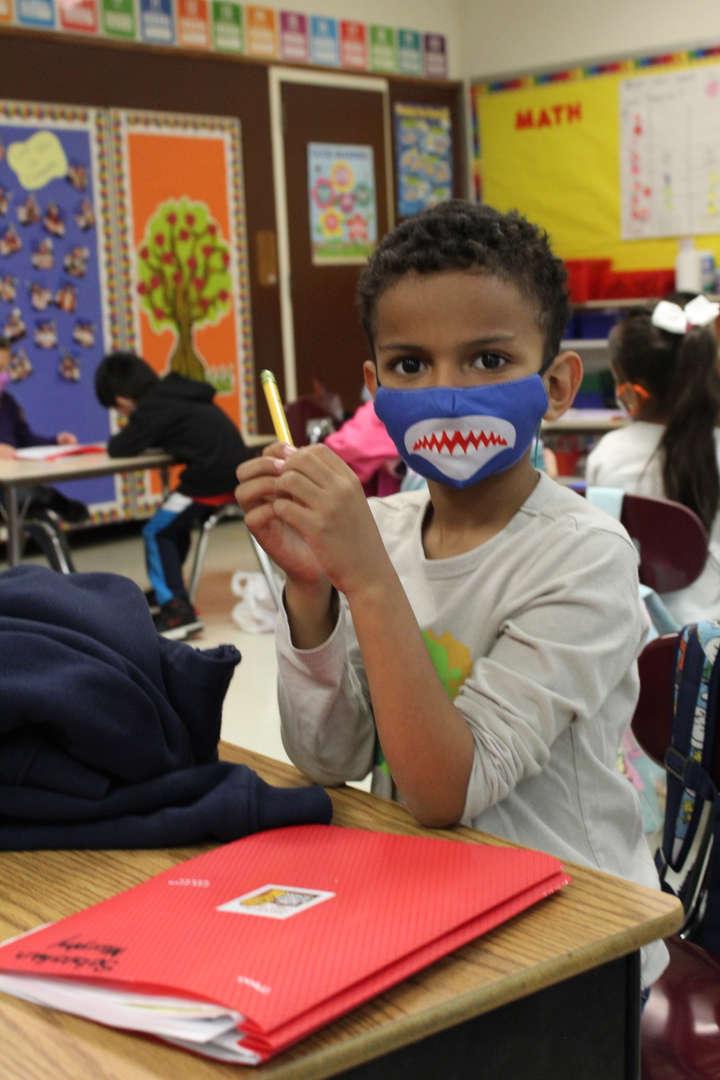 Boy with shark mask at desk