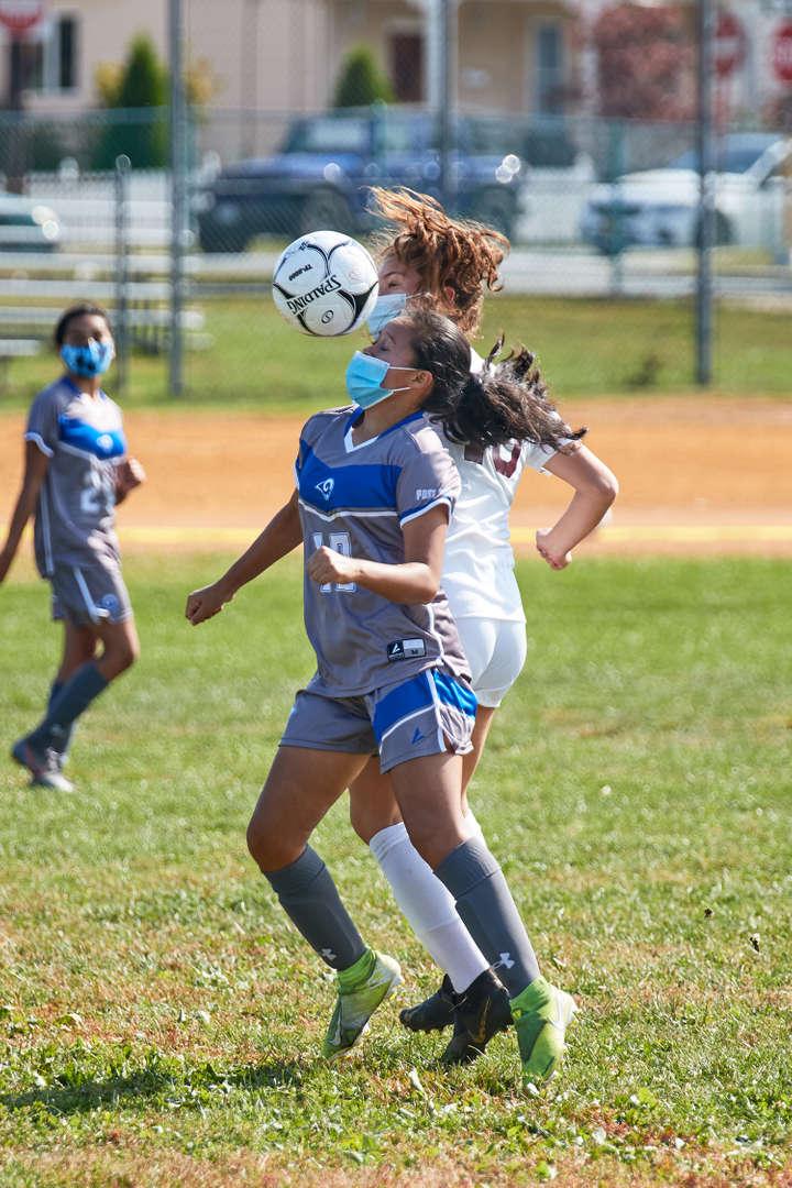 Girl hitting soccer ball off her head