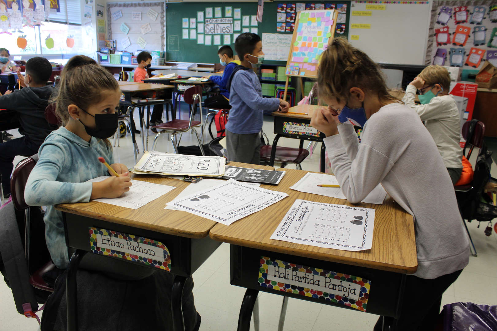 Two girls seated at desks working on homework