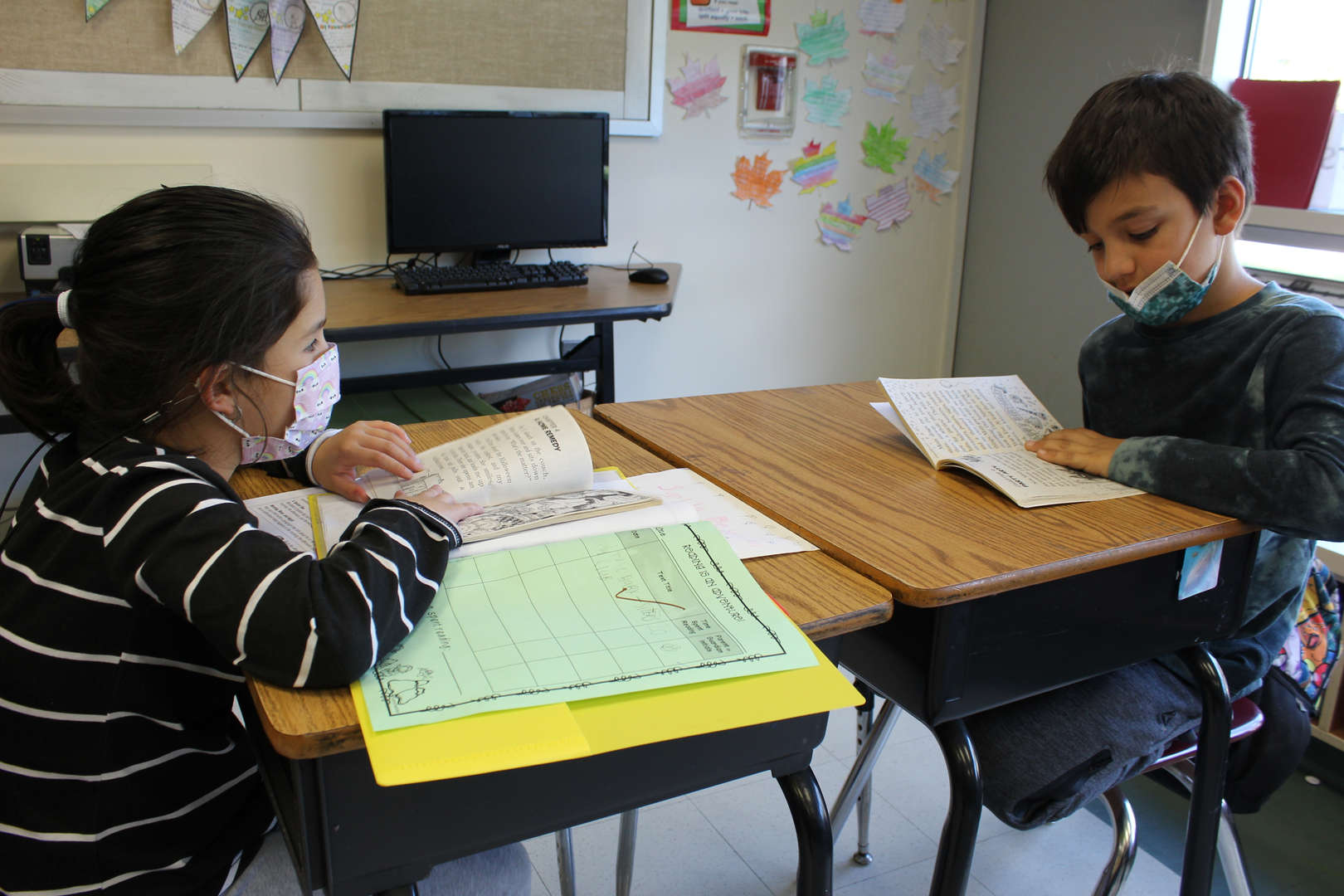 Boy and girl seated at desks reading