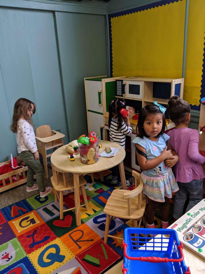 Children play in play kitchen