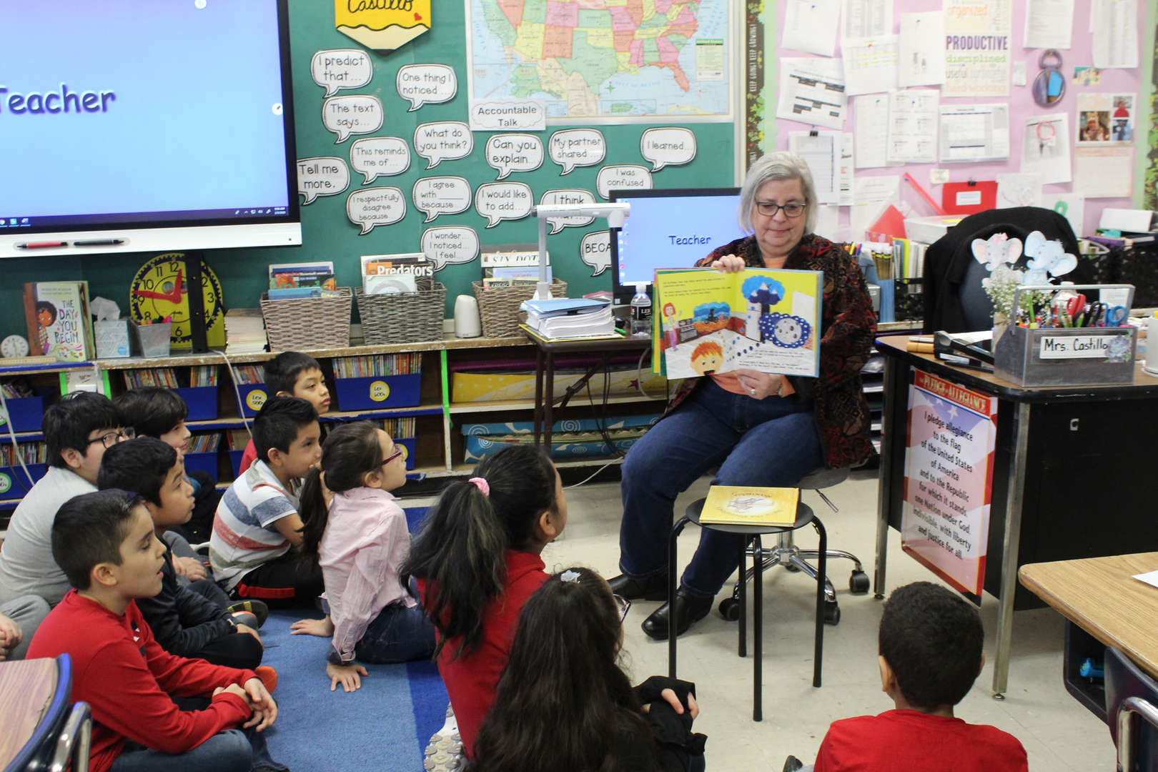 Woman shows pictures in a book to children