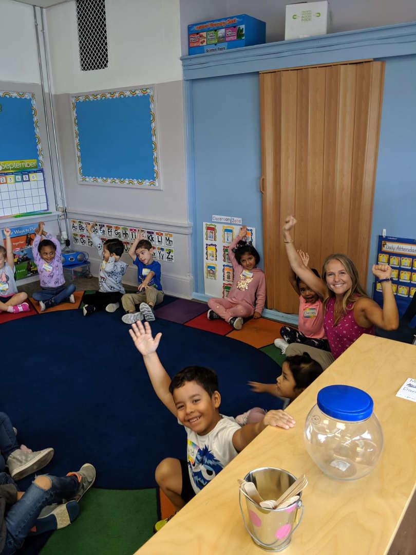 Children raise hands in response to teacher