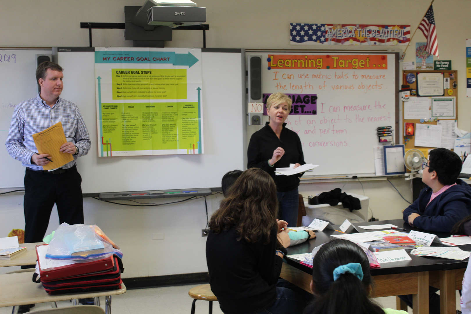 Adult volunteers speak with students in a classroom