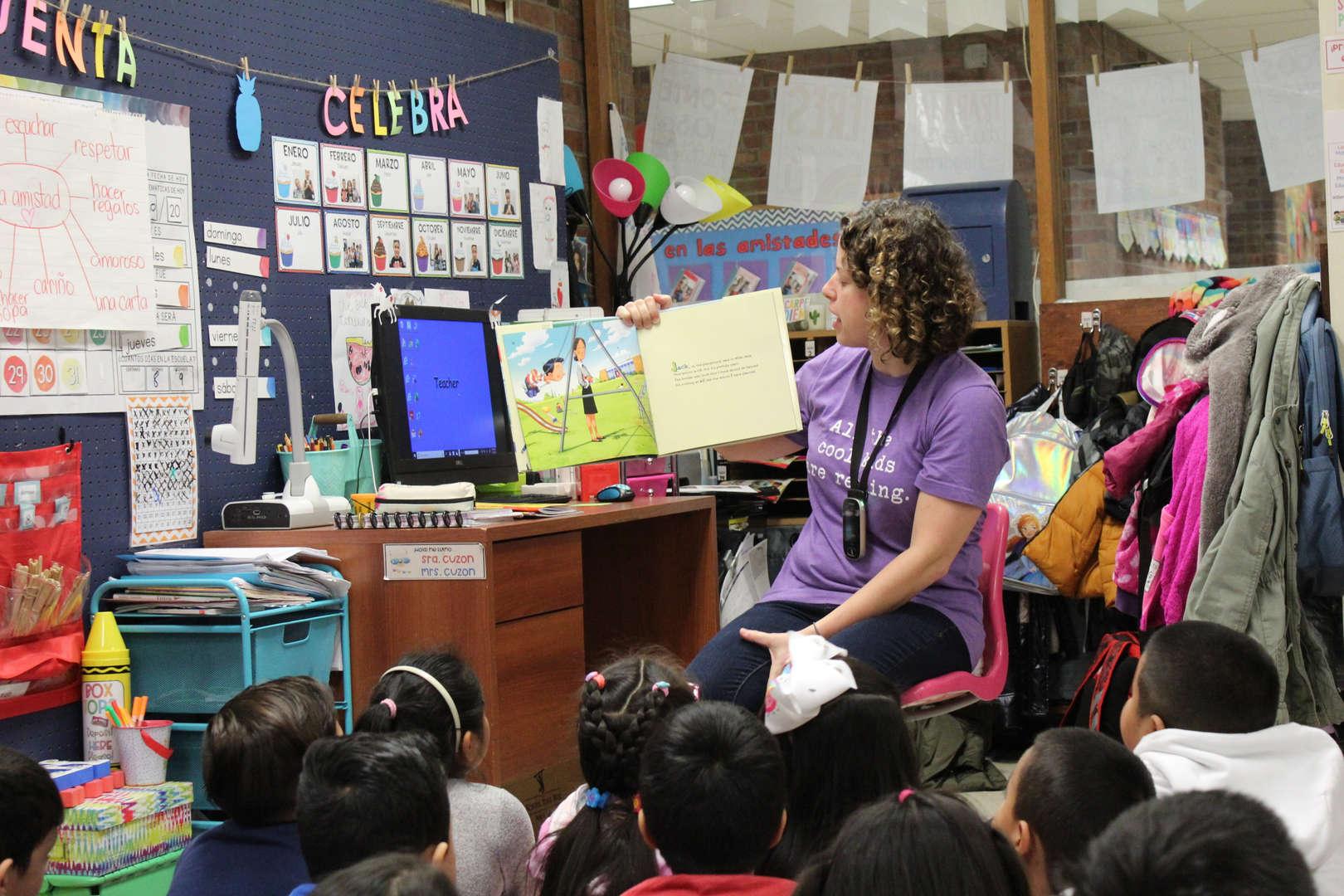Children listen as woman reads to them
