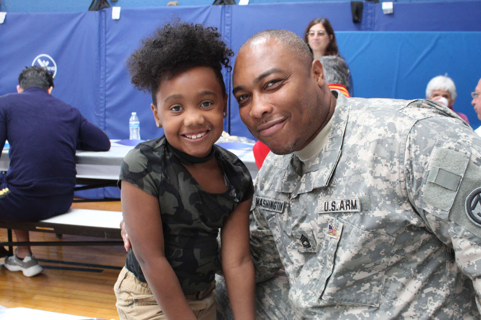 Soldier in fatigues sits next to young girl