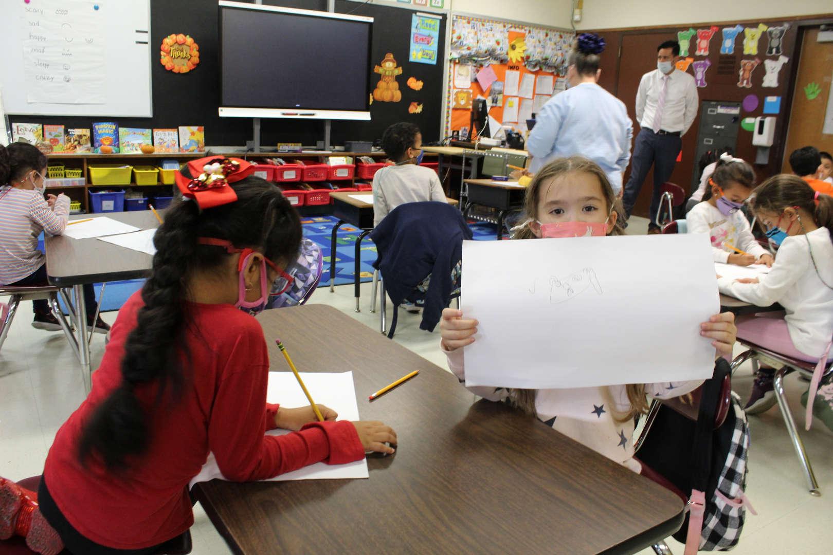 Girl holds up her artwork