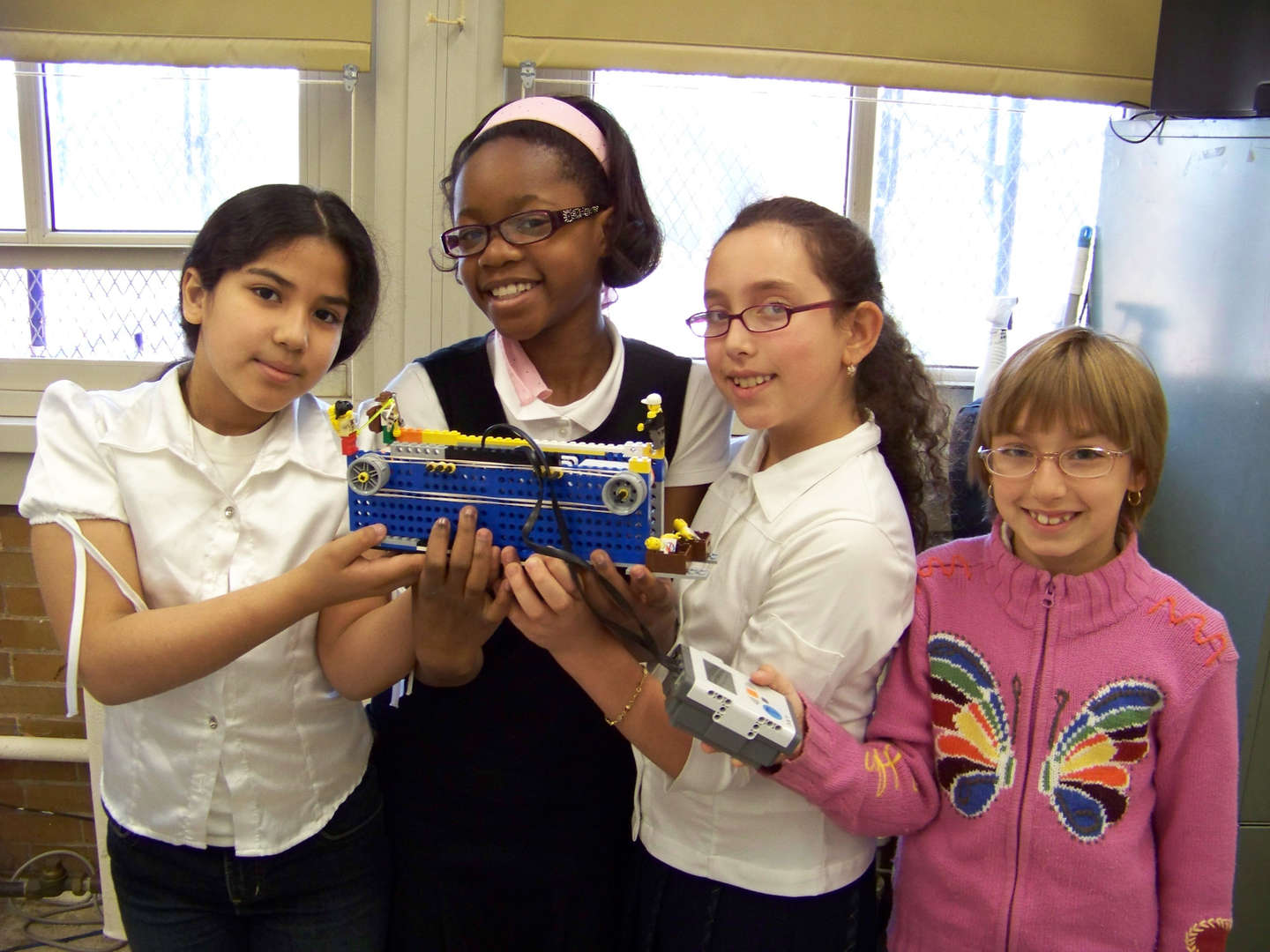 Students holding a conveyor belt for Lego Robotics