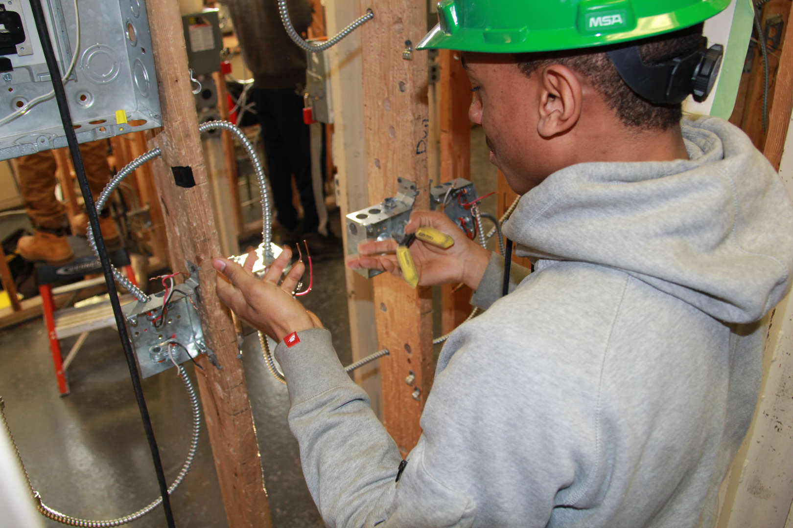 Student installing an electrical switch