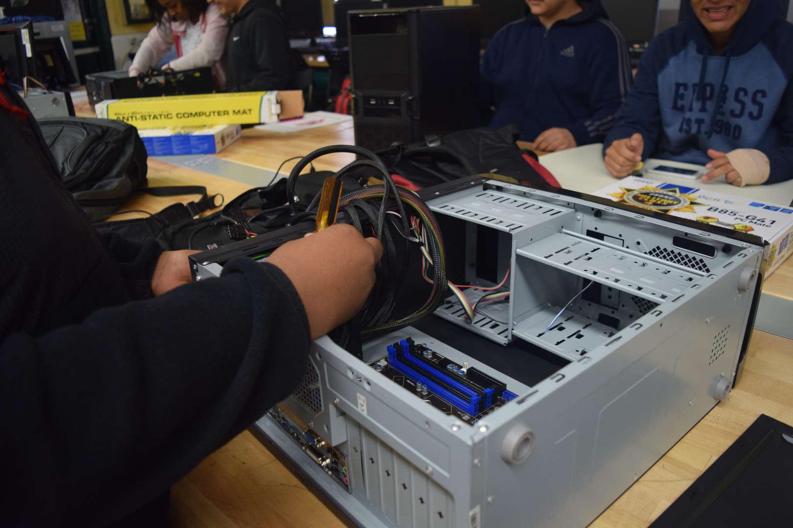 Student fixing computer hardware