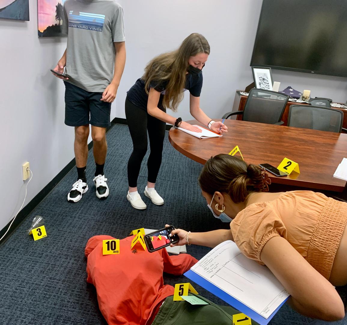 Students investigate a mock crime scene set-up