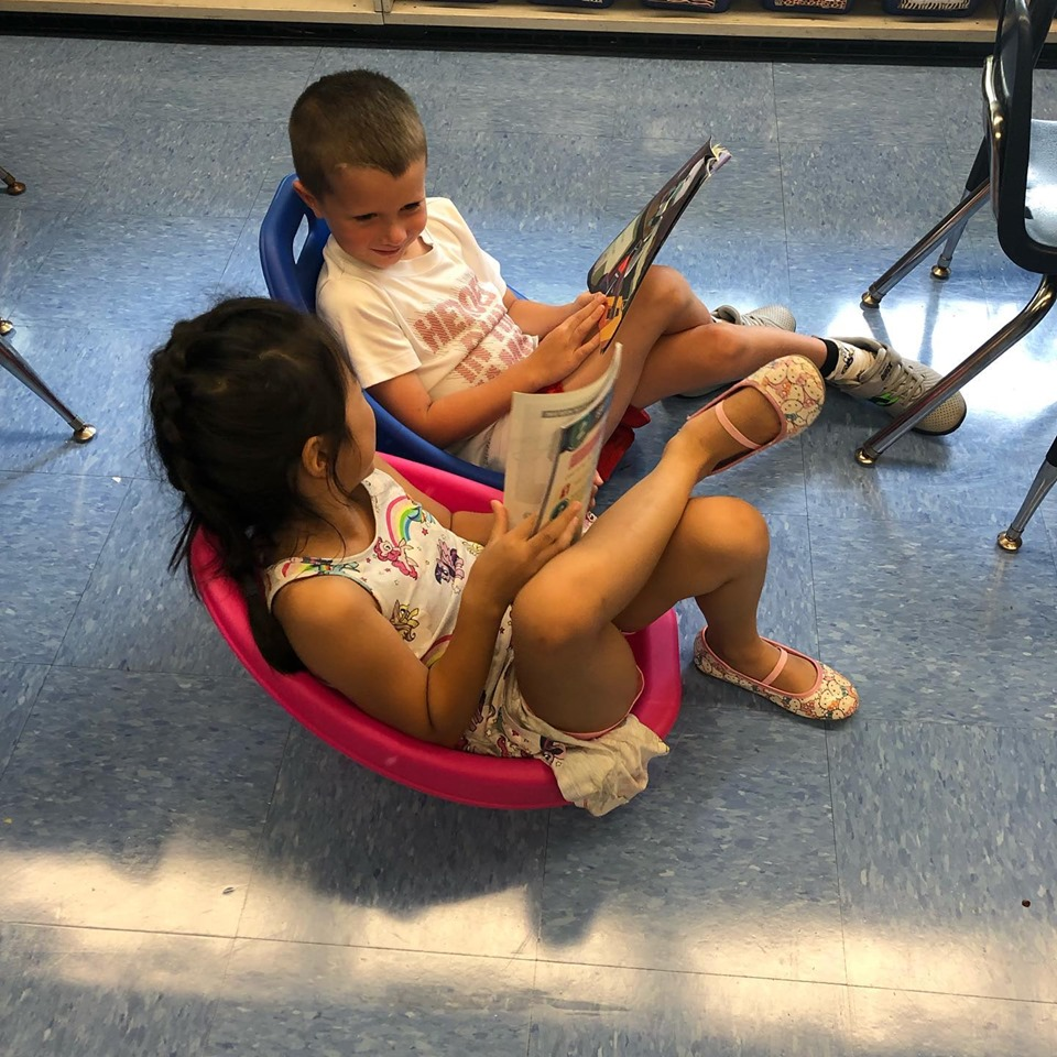 2 children in seats reading
