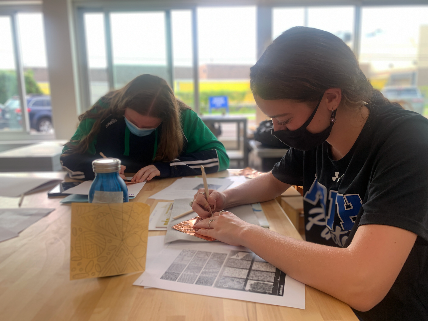 Students work on metalsmithing in art classroom