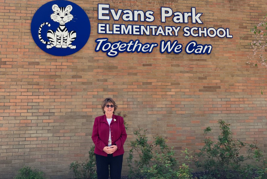 Principal stands in front of school entrance